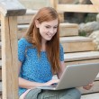 Smiling woman working on a laptop — Stock Photo #26089251