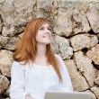 Foto Stock: Happy woman with her laptop in the garden