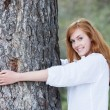 Pretty woman hugging a tree — Stockfoto