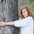 Pretty woman hugging a tree — 图库照片