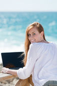 Woman using a laptop at the sea — Stock Photo