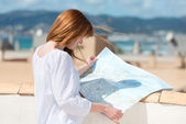 Woman consulting a map on an urban rooftop — Stock Photo