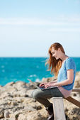 Femme travaillant sur son ordinateur portable en bord de mer — Photo