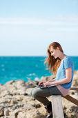 Vrouw die werkt op haar laptop aan de kust — Stockfoto
