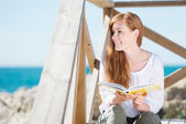Woman relaxing with a book at the sea — Stock Photo