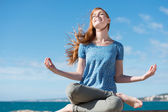 Beautiful woman meditating at the seaside — Stock Photo