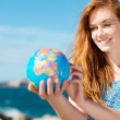 Smiling woman holding a globe at the sea — Stok fotoğraf