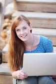 ラップトップで屋外に働く女性の笑みを浮かべてください。 — ストック写真