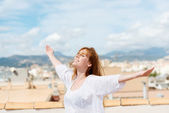 Woman on a rooftop embracing the sunshine — Stock Photo