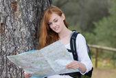 Mochilero de mujer con un mapa — Foto de Stock