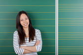 Smiling female student with crossed arms — 图库照片