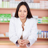 Smiling female pharmacist leaning on counter — Stock Photo