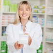 Pharmacist passing medicine box — Stock Photo #26133055