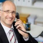 Businessman Using Landline Phone At Desk — Stock Photo