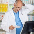 Pharmacist Holding Prescription Paper At Counter — ストック写真