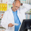 Pharmacist Holding Prescription Paper At Counter — Stock Photo