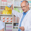 Pharmacist Taking Out Prescribed Medicine For Customer — Stock Photo #26135389