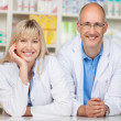 Stock Photo: Pharmacists Leaning On Pharmacy Counter