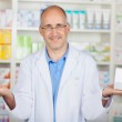 Pharmacist showing apple and medicin — Stock Photo #26135969