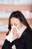 Young woman with a cold using paper tissue — Stock Photo