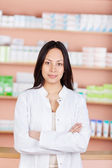 Young saleswoman with folded arms in a drug store — Stock Photo
