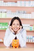 年轻女售货员在药店与猪存钱罐 — 图库照片