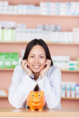 Young saleswoman in drug store with piggy bank — Stock Photo