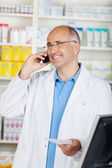 Cheerful mature pharmacist on the phone — Stock Photo