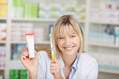 Pharmacist Holding Toothpaste And Toothbrush In Pharmacy — Stock Photo
