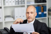 Serious businessman studying paper — Stock Photo