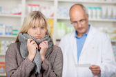 Woman Shivering With Male Pharmacists Reading Prescription — Stock Photo