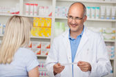 Confident mature pharmacist in customer interview — Stock Photo