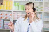 Pharmacist Conversing On Headset While Holding Prescription Pape — Stock Photo