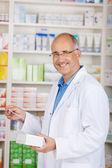 Pharmacist Holding Medicine And Prescription Paper In Pharmacy — Stock Photo
