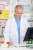 Pharmacist looking at computer — Stock Photo