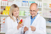 Pharmacist With Female Coworker Holding Medicine And Prescriptio — Stock Photo