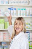 Kvinnliga farmaceut tar medicin låda från hyllan — Stockfoto