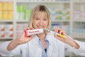Pharmacist Holding Toothpaste And Toothbrush — Stock Photo
