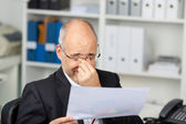 Businessman Holding Document While Rubbing Eyes — Stock Photo
