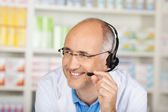 Pharmacist Conversing On Headset In Pharmacy — Stock Photo