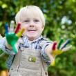 Little boy showing his painted hands outside — Stock Photo