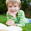 Smiling Boy Reading book in the garden — Stock Photo