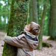 Little child embracing tree trunk — Stock Photo