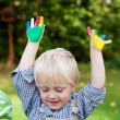 Little boy with colorful painted hands — Stock Photo