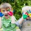 Two children showing painted hands outside — Stock Photo