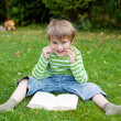 Cheerful little boy reading book on the grass — Stock Photo