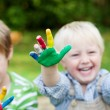 Laughing children showing colorful painted hands — Stock Photo