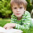 Young boy looking up from reading a book — Stock Photo