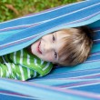 Cheerful child playing in blue hammock — Stock Photo