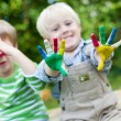 Happy children playing with finger paint — Stock Photo